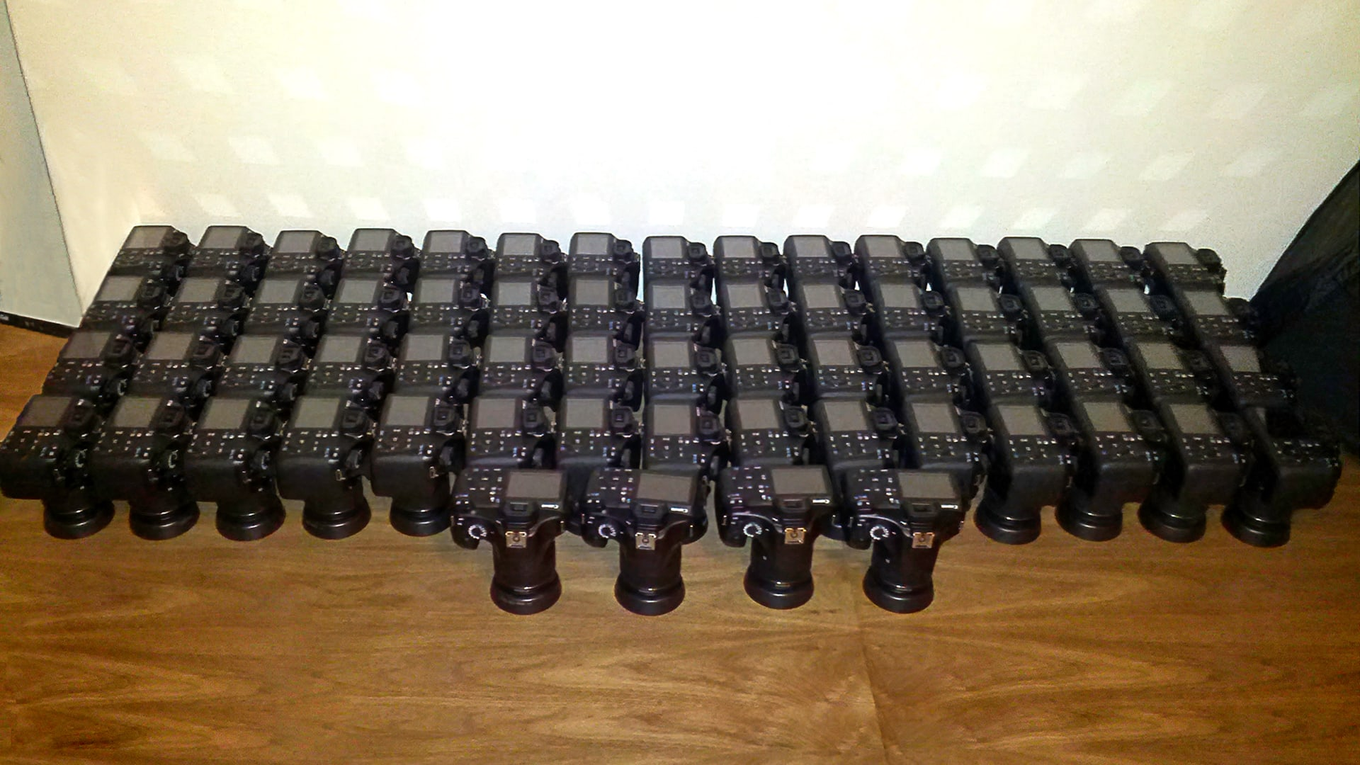 64 DSLR Cameras on a table